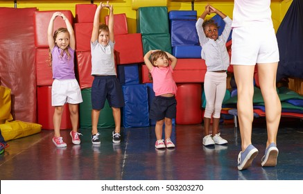 Kids gymnastics with group of children in physical education with PE teacher