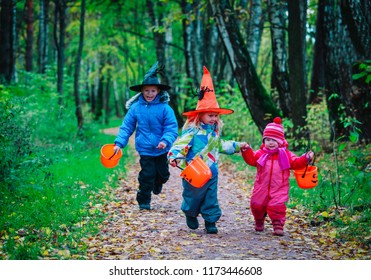 kids in halloween costume trick or treating in autumn nature