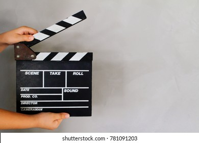 Kid's hand holding film clapper board with gray concrete loft style wall background texture. Concept for movie and video production, film director.