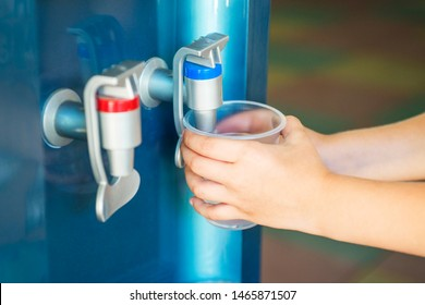 Kid's hand holding the glass with water from the water cooler. Little child press the drinking water.