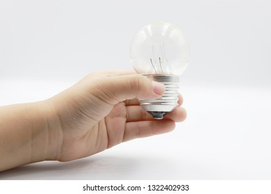 Kids hand holding a light bulb isolated on white background.