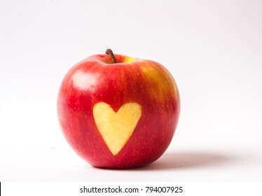 Kid's hand holding red apple with heart -shaped cut out. Love fruits - source of vitamins Healthy nutrition concept.