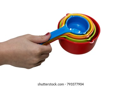 Kid's hand holding the set of colorful plastic measuring spoons isolated on white background.