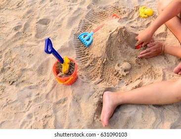 Kid's hand molding sandcastles and children's beach toys at the beach.