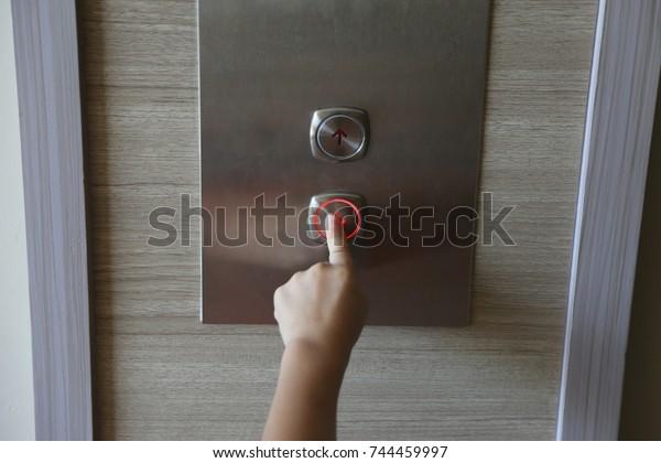 kid's hand press down button of elevator