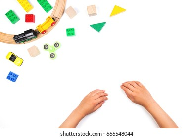 Kid's hands and colorful toys. Fidget spinner, cars, toy train, rails, bricks and blocks on white background