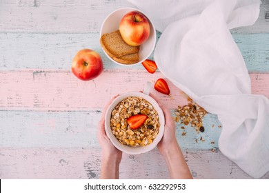Kids hands holding bowl with healthy breakfast with granola and apples