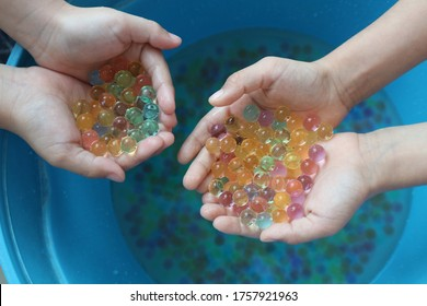 Kids' hands holding Colorful Hydrogel Balls or Aqua Crystal Jelly Beads Soil for Flower or Plant or Home Decoration isolated on white background.