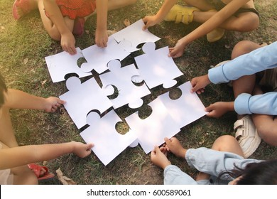 Kids hands holding jigsaw/ puzzle pieces on grass. concept: cooperation, teamwork, learning and education . Selective focus.