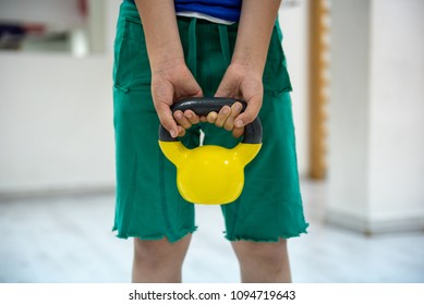 Kid's hands holding kettle bell for exercising arms and shoulders. Having fun in gym, waiting for his father to finish his training.