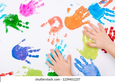 Kid's hands making colored handprints on white background. Top view, flat lay.