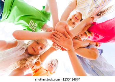 Kids hands together in circle laying one on another