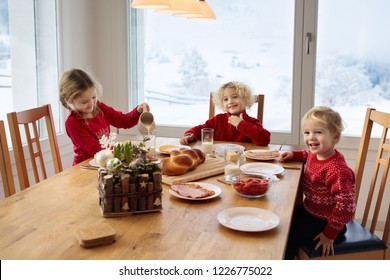 Kids having breakfast on Christmas morning. Family eating bread and drinking milk at home on snowy winter day. Children eat in sunny dining room at window with Swiss mountains and snow view.