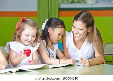 Kids having fun drawing in kindergarten with a nursery teacher