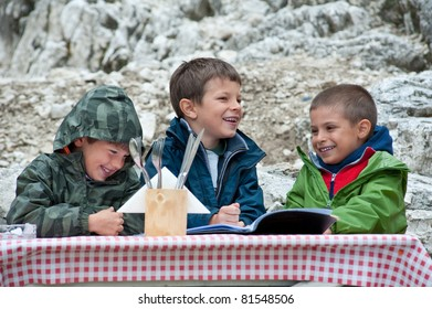 Kids having fun during lunch in a mountain refuge. Dolomites, Italy.