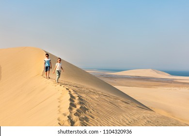 Kids having fun exploring together sand dunes in Qatar desert