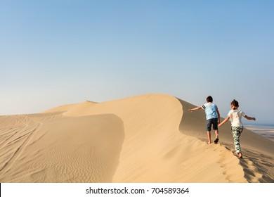 Kids having fun playing together at sand dunes in Qatar desert