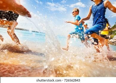 Kids having fun run make splashes in shallow water