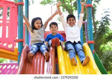 Kids having fun and sliding on outdoor playground. Kids Enjoying