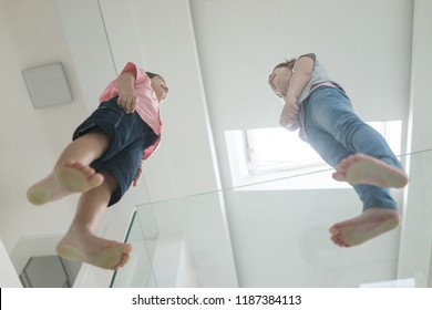 Kids having fun standing on glass in modern futuristic smart home interior