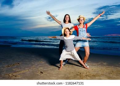 Kids having fun at sunset beach - friendship freedom beach summer holiday concept