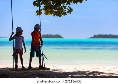 Kids having fun swinging at beach on summer vacation
