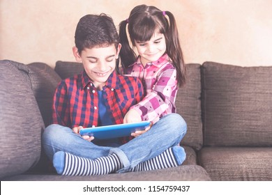 Kids having fun with their tablet at home. Children and technology concept