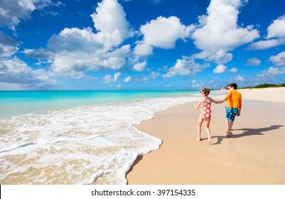 Kids having fun at tropical beach during Caribbean summer vacation playing together at shallow water