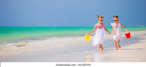 Kids having fun at tropical beach playing together at shallow water