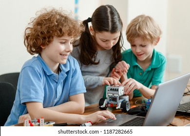Kids having fun in workshop. Building a robotic toys and programming them using a computer. Innovative education.