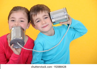Kids having a phone call with tin cans on yellow background