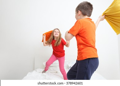 kids having a pillow fight in bed
