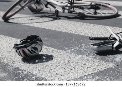 Kid's helmet and broken car's mirror next to broken bicycle on pedestrian crossing