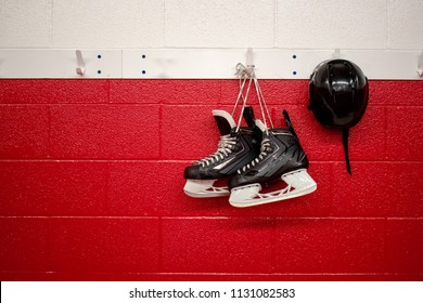 Kids Hockey skates and gloves in locker room with red background and copy space