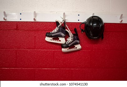 Kids hockey skates and helmet hanging on locker room with copy space