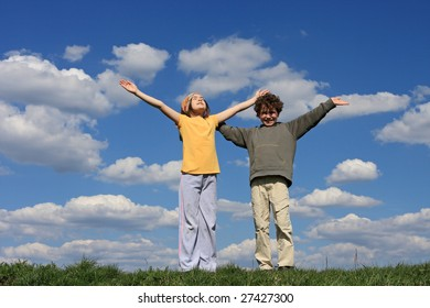 Kids holding arms up against blue sky