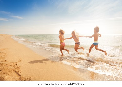 Kids holding hands and running along sandy beach
