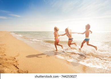 Kinder, die Händen halten und am Sandstrand entlang laufen