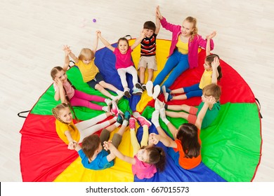 Kids holding hands together with teacher in gym