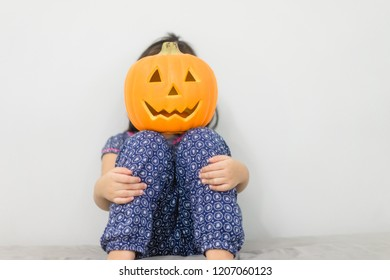 Kid's holding Jack'O pumpkin basket to collect candy trick or treat on Halloween day.Asian little girl want to go to collect candy in Halloween night.Concept for Halloween holiday.