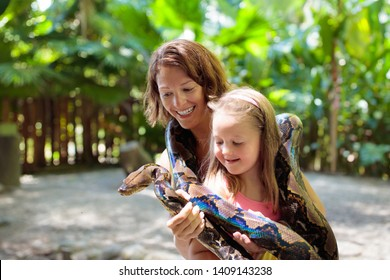 Kids holding python snake in tropical zoo. Family watching exotic reptile. Mother and child with snakes on trip to safari park. Brave kid learning to overcome fear and phobia. Rainforest animals.