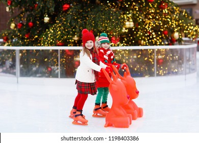 Kids ice skating in winter park rink. Children ice skate on Christmas fair. Little girl and boy with skates on cold day. Snow outdoor fun for child. Winter sports. Xmas family vacation with kid.