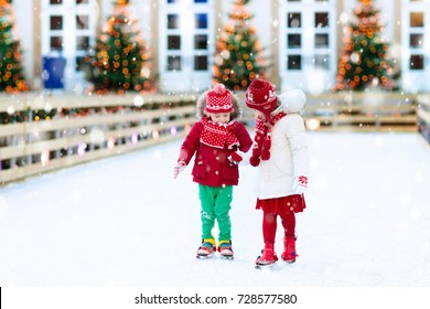 Kids ice skating in winter park rink.
