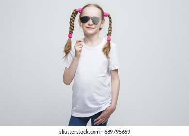 Kids Ideas and Concepts. Portrait of Positive Caucasian Blond Girl With Pigtails Posing with Artistic Spectacles Against White Background. Horizontal Image