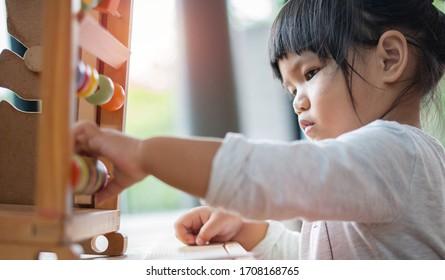 Kinder lernen von Spielen mit buntem Holzspielzeug auf dem Tisch zu Hause. Junge Preschool-Mädchen konzentrieren sich mit Bildungsausrüstung in der Pause zurück zu Schule Kinder zu Hause oder Kindergarten.
