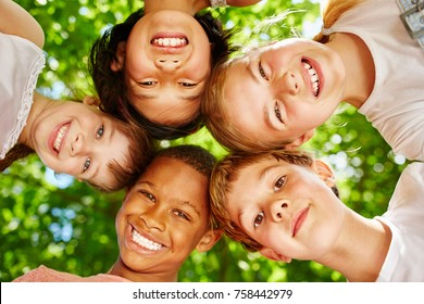 Kids as international team in a circle smiling in summer