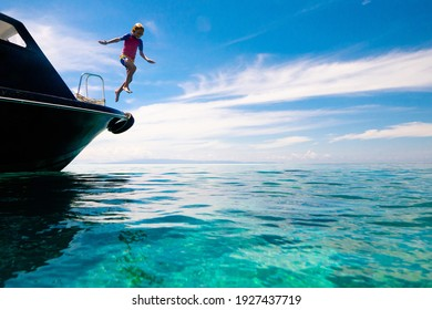 Kids jump into sea. Yacht vacation with child on exotic tropical island with crystal clear water. Beach and swim fun. Sailing and cruise with children. Summer holiday on boat. Little boy swimming.