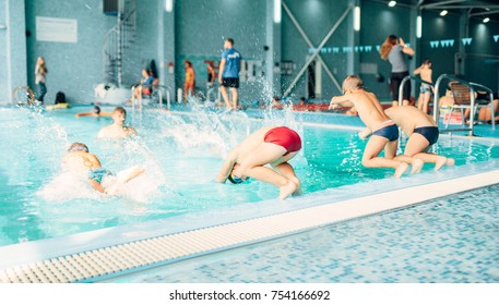 Kids jumping into pool with clean blue water