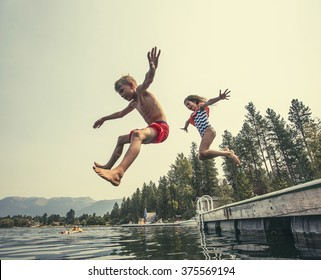 Kids jumping off the dock into a beautiful mountain lake. Having fun on a summer vacation at the lake with friends - Shutterstock ID 375569194