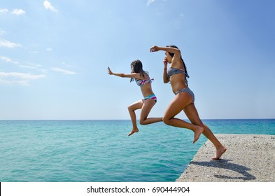 Kids jumping off the dock into a turguise sea water. Having fun on a summer vacation with friends